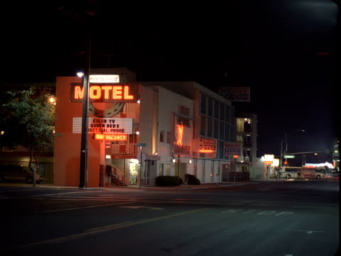 ws, motel illuminated at night, buildings and street intersection in background, reno, nevada, usa - nevada stock videos & royalty-free footage