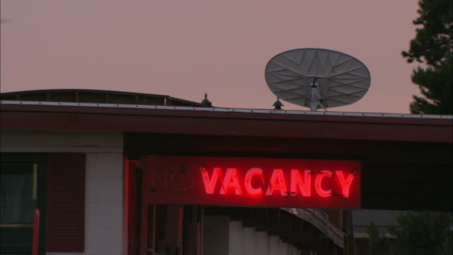 A motel's neon vacancy sign glows brightly under a satellite dish.