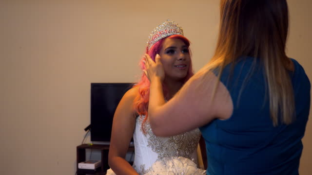 ms pan mother adjusting daughters crown in home before quinceanera - 14 15 anni video stock e b–roll