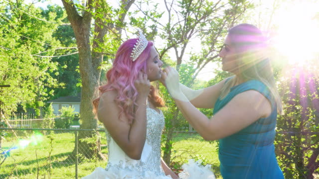 ms mother adjusting daughters hair in backyard before quinceanera - anticipation stock-videos und b-roll-filmmaterial