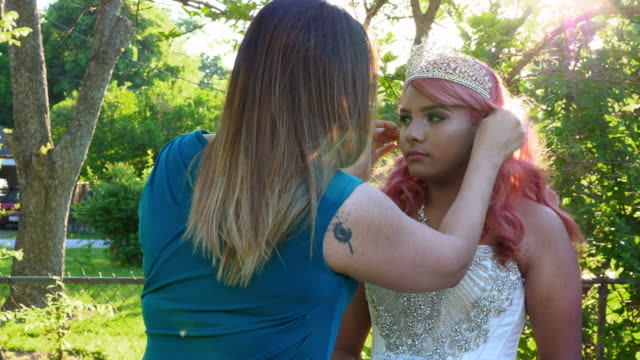 ms mother adjusting daughters hair in backyard before quinceanera - 14 15 anni video stock e b–roll