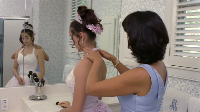 Mother adjusting Quinceanera dress worn by daughter / they hug