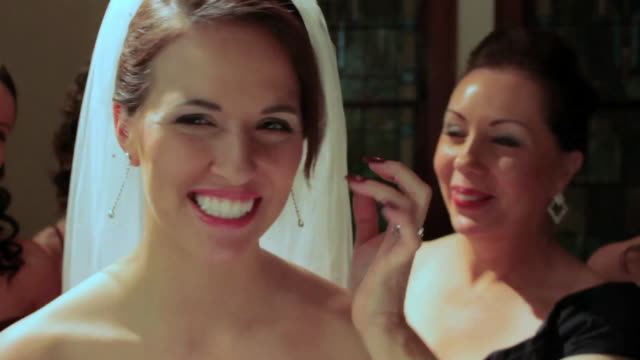 mother adjusts brides veil and bridesmaid helps with necklace - earring stock videos and b-roll footage
