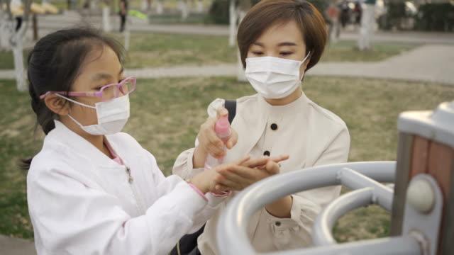 stockvideo's en b-roll-footage met moeder alcohol spray en veeg hand voor kill kiemen met dochter - china east asia