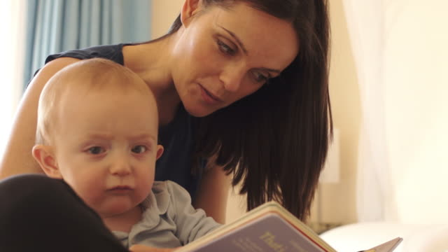 mother and 12 month old baby  reading on bed indoors. - dreiviertelansicht stock-videos und b-roll-filmmaterial