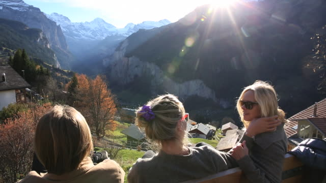 Mother and 2 adult children relax above mountain valley, talking together