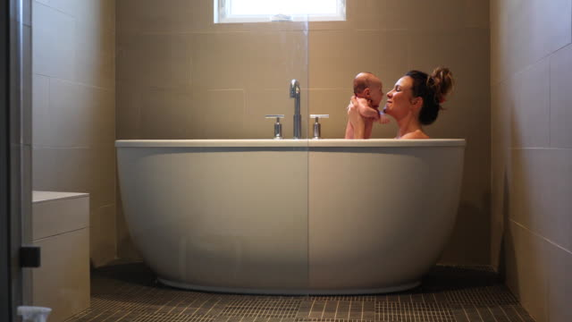 a mother and a new born baby taking his first bath. - taking a bath stock videos & royalty-free footage