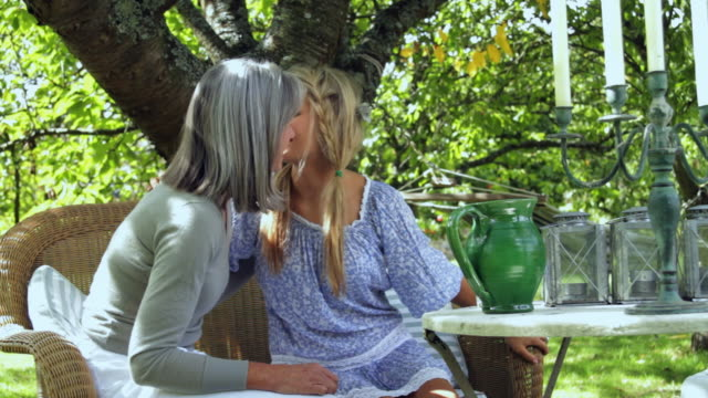 MS Mother and adult daughter in garden greeting, talking and drinking water / London, United Kingdom