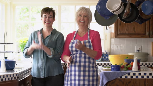 ms mother and adult daughter wiping their hands together after cooking - domestic kitchen stock videos & royalty-free footage