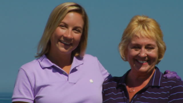 cu, tu, mother and adult daughter with golf clubs, portrait, north truro, massachusetts, usa - maglietta polo video stock e b–roll