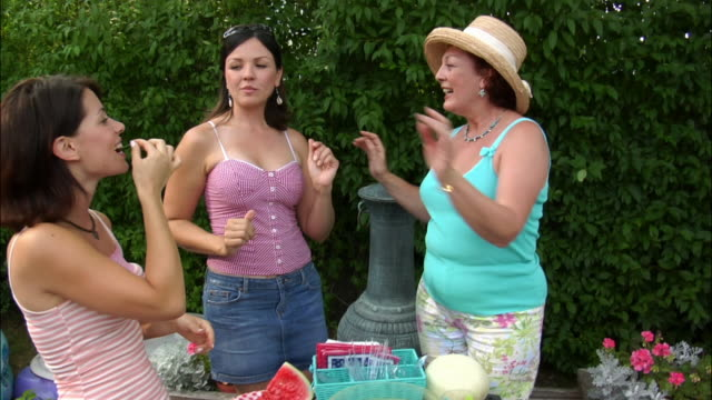 Mother and adult daughters dancing and eating next to barbecue grill / New Jersey