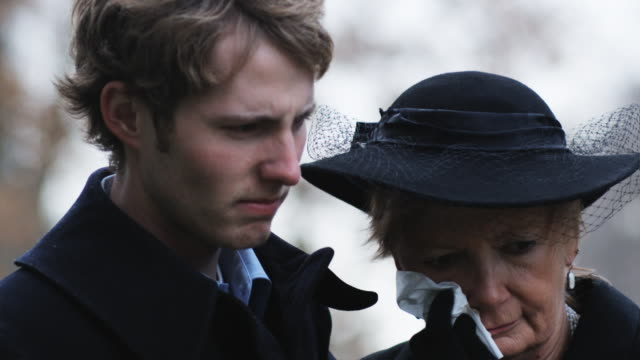 mother and adult son at a funeral - begräbnis stock-videos und b-roll-filmmaterial