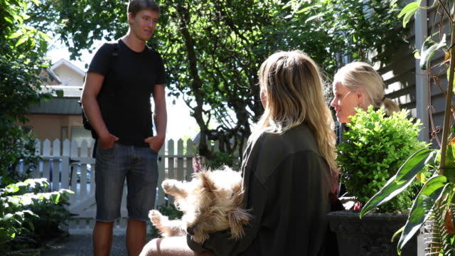 Mother and adults kids relax in garden setting, talking