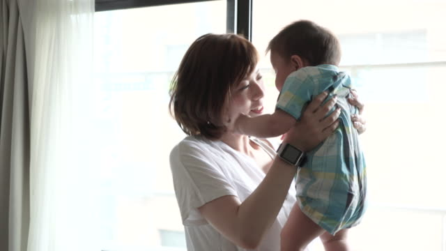 Mother and Baby Boy having fun time in house.