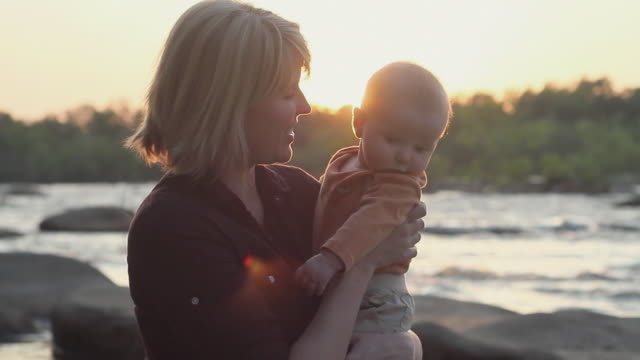 cu mother and baby boy (2-5 months) hugging on riverbank at sunset / richmond, virginia, usa - 2 5 months stock videos & royalty-free footage