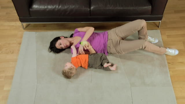ws mother and baby boy (6-11 months) playing on carpet / london, uk  - 6 11 months stock videos & royalty-free footage