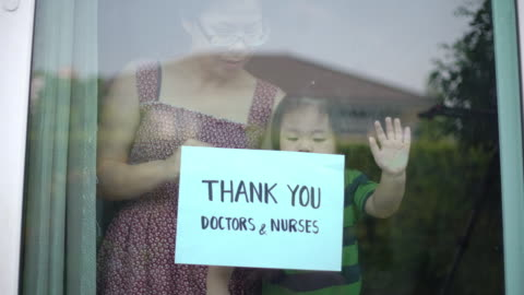 mother and baby boy showing thank you doctors and nurses sign at home for encouraging doctors and nurses in covid-19 coronavirus situation - positive emotion stock videos & royalty-free footage