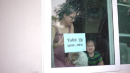Mother and baby boy showing Thank you Doctors and Nurses sign at home for encouraging Doctors and Nurses in covid-19 coronavirus situation