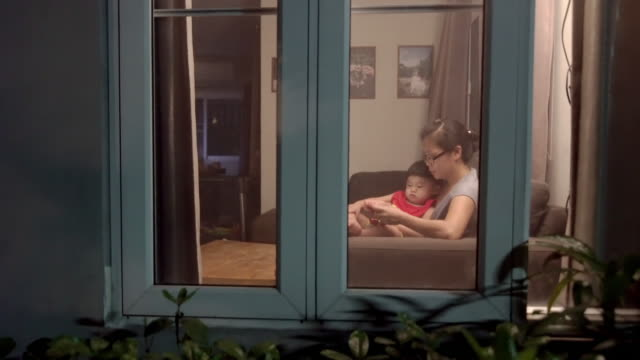 mother and baby boy watching smartphone together on sofa in living room at home in the evening - indoors stock videos & royalty-free footage