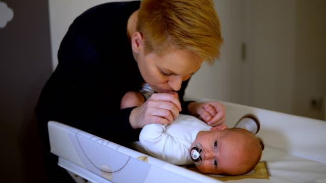 vídeos y material grabado en eventos de stock de madre y bebé cambian pañal. niño sobre el cambiador de pañal seco y limpio. - cambiar pañal
