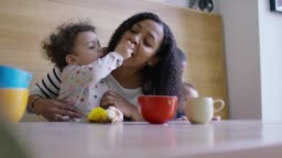 A mother and baby daughter eating some fruit together at breakfast
