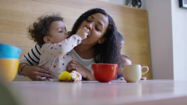 vídeos de stock e filmes b-roll de a mother and baby daughter eating some fruit together at breakfast - família monoparental