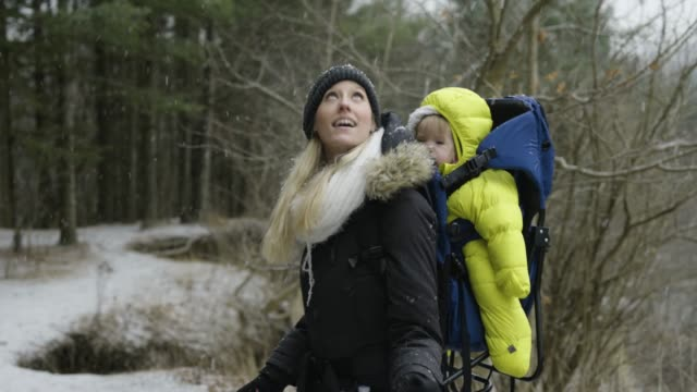 mother and baby daughter going on a hiking adventure in winter. - baby carrier stock videos & royalty-free footage