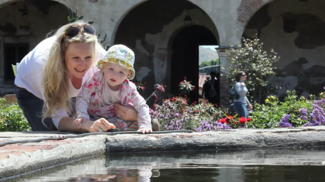 ms mother and baby daughter (12-17 months) looking at fountain, san juan capistrano, california, usa - 12 17 months stock videos & royalty-free footage