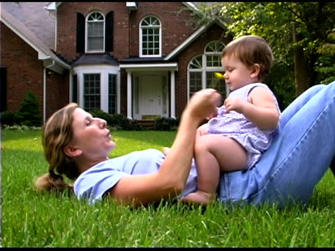 mother and baby daughter playing outdoors - lying on back stock videos & royalty-free footage