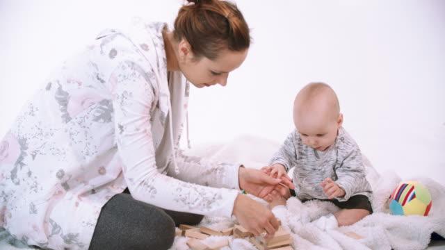 mother and baby daughter playing - abbigliamento da neonato video stock e b–roll