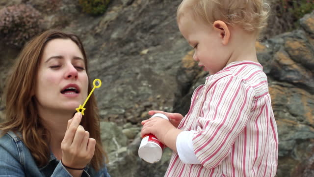 cu pan mother and baby girl (18-23 months) blowing bubbles on beach / big sur, california, usa - 18 23 months bildbanksvideor och videomaterial från bakom kulisserna