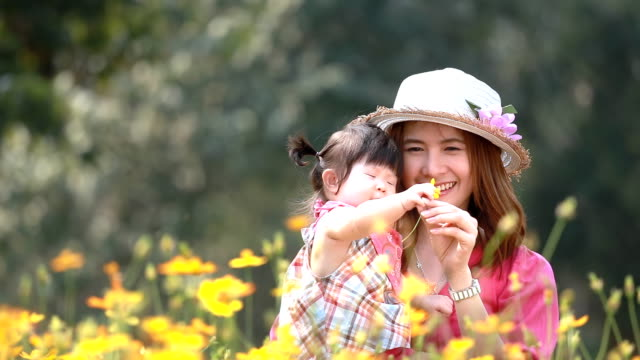 Mother and baby girl  in yellow flower field