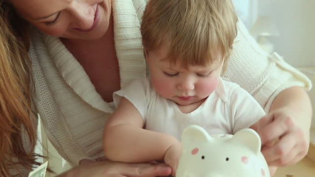cu td mother and baby girl (12-23 months) putting coins into piggy bank / jersey city, new jersey, usa - tutina video stock e b–roll