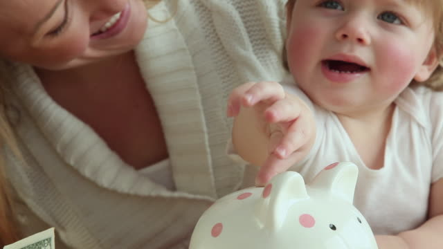 cu mother and baby girl (12-23 months) putting coins into piggy bank / jersey city, new jersey, usa - savings stock videos and b-roll footage