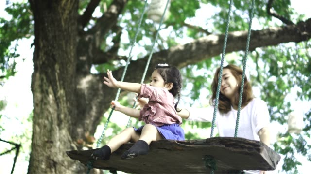 Mother and baby girl swinging in the park
