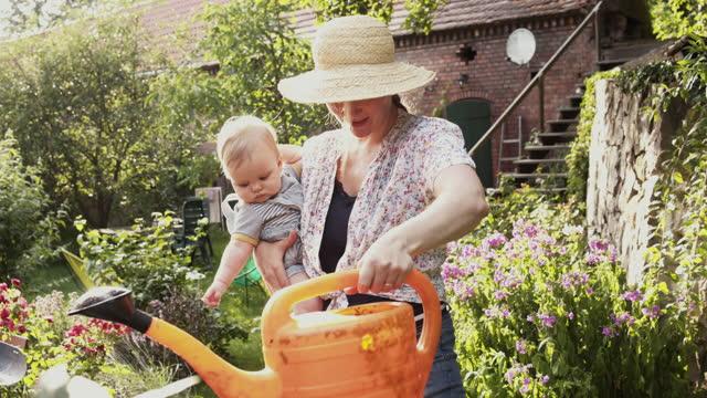vídeos y material grabado en eventos de stock de mother and baby girl taking water from water barrel for own organic garden. - conservacionista