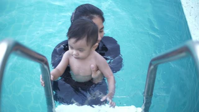 stockvideo's en b-roll-footage met slo mo moeder en baby plezier in zwembad - buitenbad