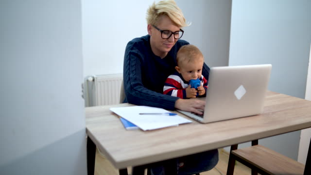 mother and baby in dining room with laptop smiling - working mother stock videos & royalty-free footage