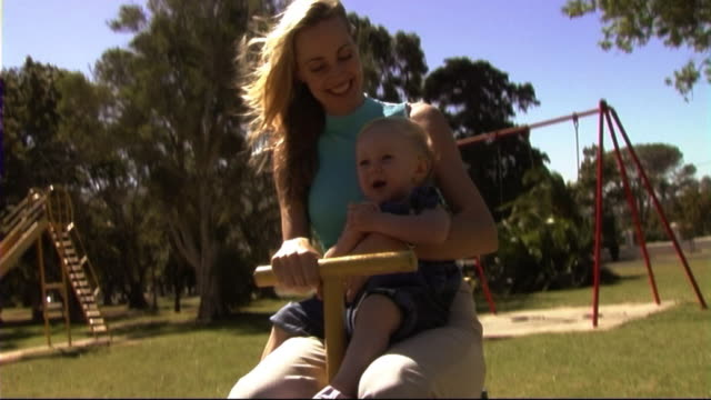 stockvideo's en b-roll-footage met mother and baby in park in roundabout - 2005