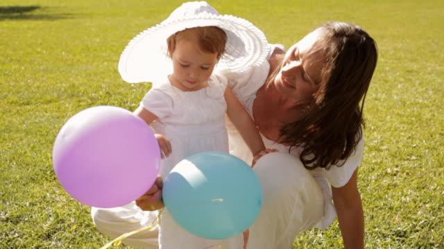 vídeos y material grabado en eventos de stock de mother and baby in park - three quarter length