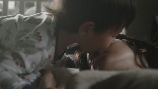 stockvideo's en b-roll-footage met moeder en baby kussen op bed - kussen beddengoed