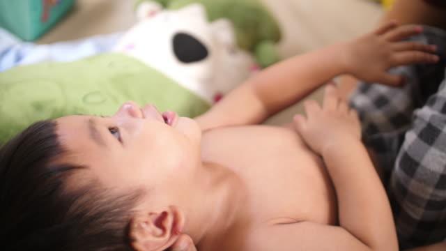 母と赤ちゃんが横たわっているとの時間を一緒に過ごす - 生後1ヶ月点の映像素材/bロール