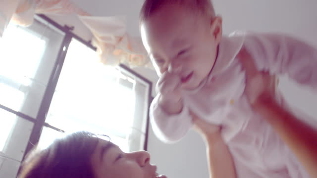 Mother and baby playing and smiling on bed