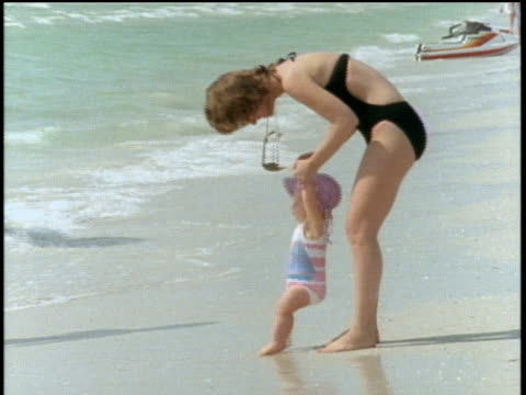 vídeos de stock e filmes b-roll de mother and baby playing at the beach in st petersburg florida - 1980