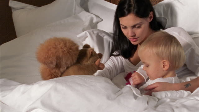 mother and baby playing in bed with squirrel puppet - puppet stock videos & royalty-free footage