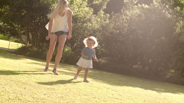 vídeos de stock e filmes b-roll de mother and baby playing in park running towards camera - família com um filho