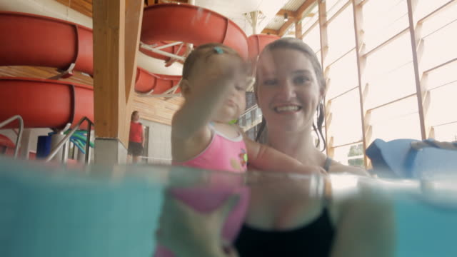 ms mother and baby playing in swimming pool / vancouver, british columbia, canada - wasserrutsche stock-videos und b-roll-filmmaterial