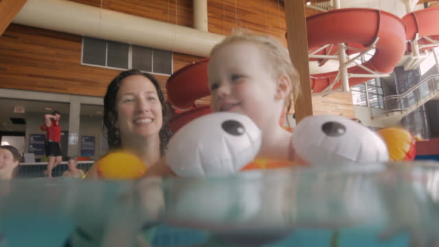 MS Mother and baby playing in swimming pool / Vancouver, British Columbia, Canada