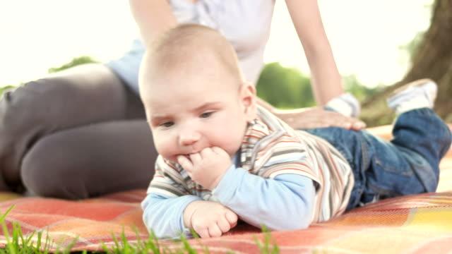 hd: mutter und baby spielen im park - saugen mund benutzen stock-videos und b-roll-filmmaterial