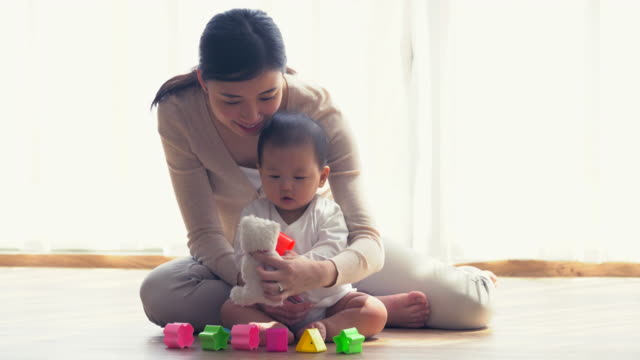 ms mother and baby playing together at home - 床点の映像素材/bロール